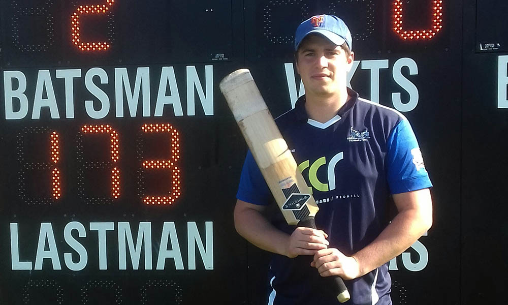 Cricketer Laurie Nicholson next to scoreboard showing his record 173 score.