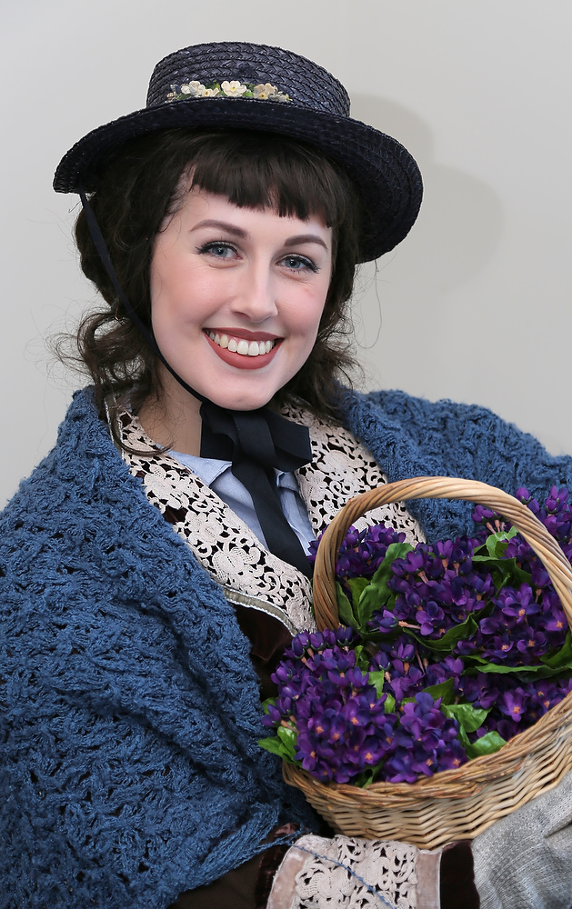 dark haired woman in period costume holding a basket of purple flowers
