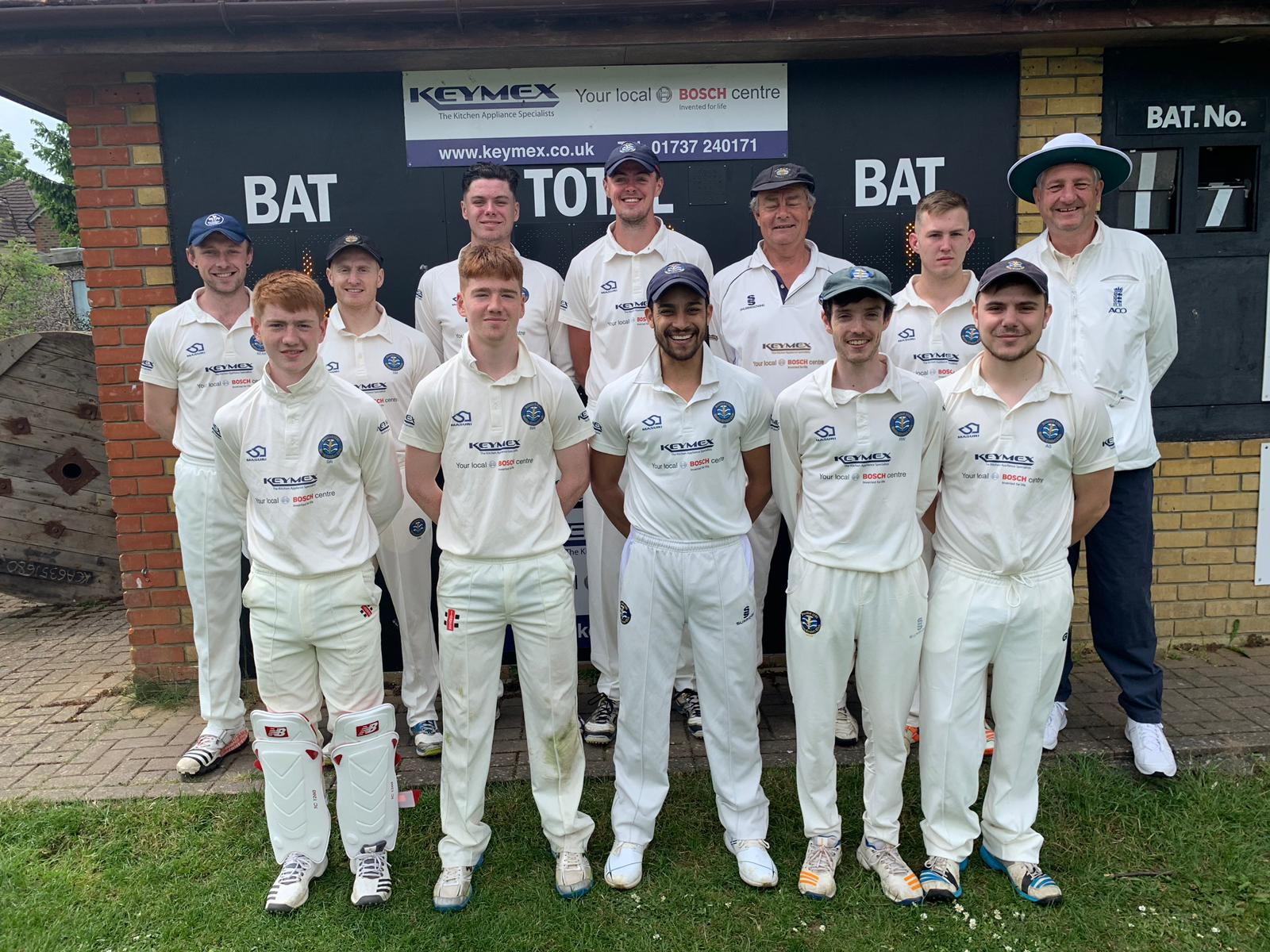 Male cricket team stand in front of scoreboard