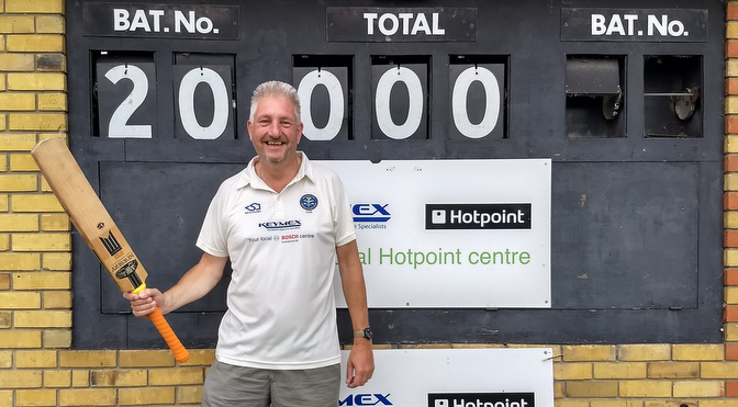 cricketer in front of scoreboard with 20000 showing