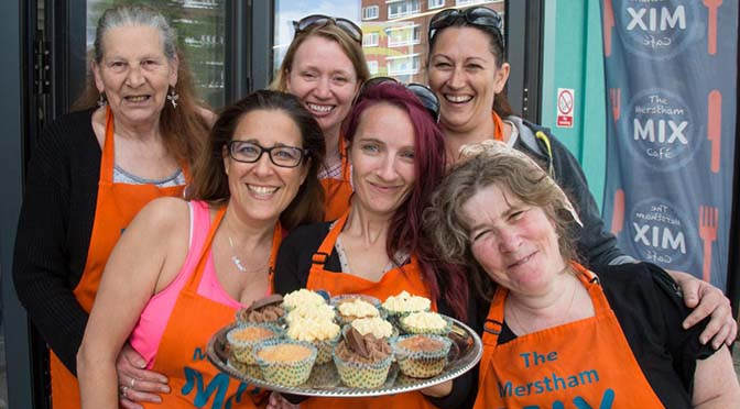group of smiling volunteers with tray of cupcakes